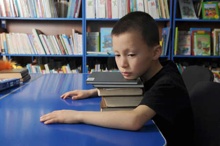 Boy lying tired on pile of books in library dont want to learning