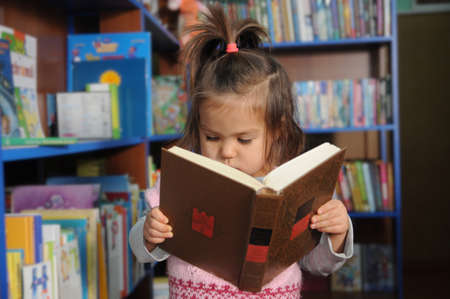 Little girl reading book in library environment