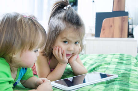 Little girls looking on pad lying on bed at home. Children time spending. Kids using tablet computer 版權商用圖片