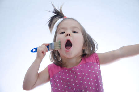 child singing song emotionally with paint brush. Artist  imagining