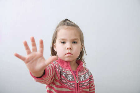 stop sign, little girls palm saying stop with hands in front of himself. suspend of constraint on children. Kids protection. Stock Photo