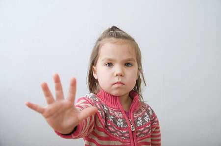 stop sign, kids palm saying stop with hands in front of himself. suspend of constraint on children. toddler protection.