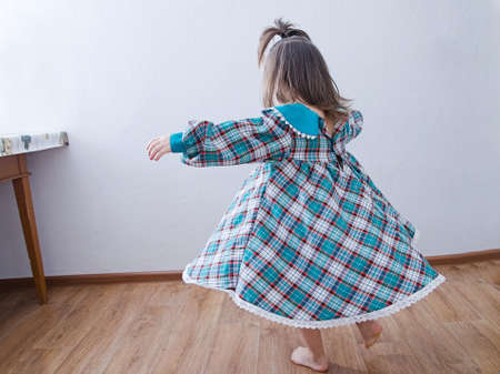 little girl dancing at home. domestic child in green dress whirling skirt