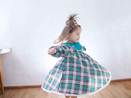 Child dancing at home. domestic kid in green dress whirling skirt 版權商用圖片