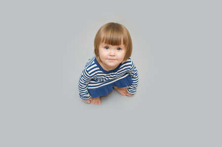 cute child portrait sitting on gray space in squatting position Imagens