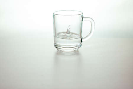 Water drop in transparent glass on gray background. purified fresh drink water on table Фото со стока