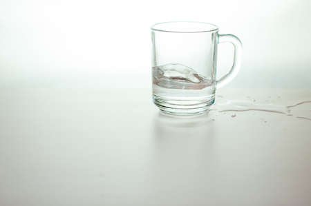 Water wave in transparent glass and puddle on gray background. purified fresh drink water on table