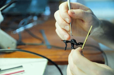 sculpting process. young man sculpting handmade toy bee from plastic glue, house decoration craftsmanship hobby, decor creation process