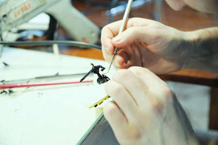 scultor at work. young man sculpting handmade toy bee from plastic glue, house decoration craftsmanship hobby, decor creation process