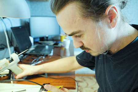 young man sculpting handmade toy bee from plastic glue, house decoration craftsmanship hobby, decor creation process