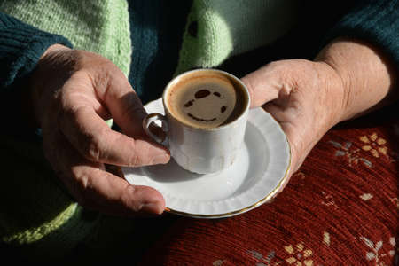 Detail of an old woman drinking Turkish coffee