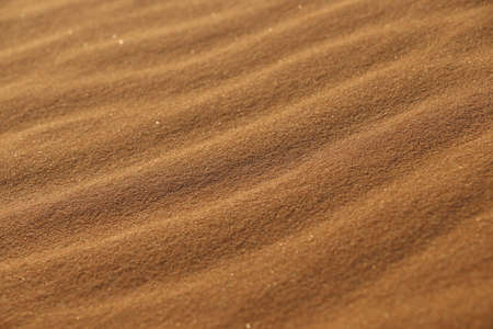 sand texture - background of desert sand dunes. Beautiful structures of sandy dunes. sand with wave from wind in desert - Close up