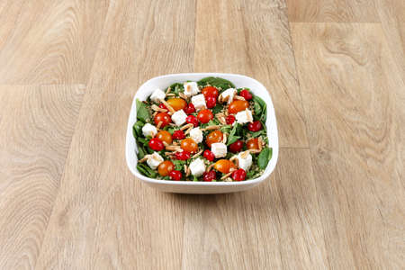 Greece salad with fresh vegetables in a withe bowel  on a wooden background