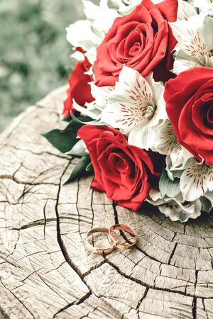 Wedding rings on a wooden background with a bouquet of roses Imagens - 142512166