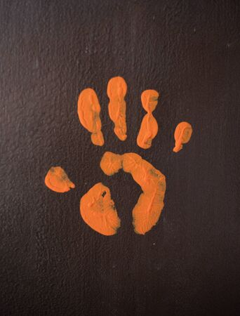 An orange palm print on a brown wall