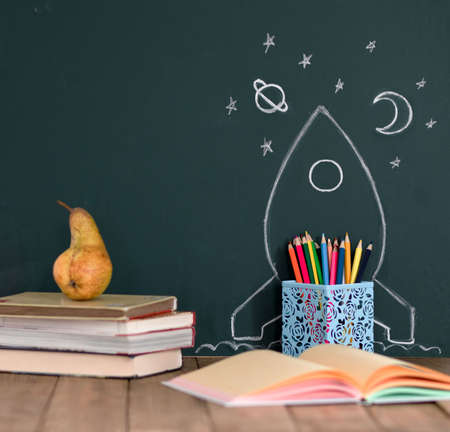 Back to School Concept with Hand Drawn Rocket and stars on Blackboard. Colored pencils and books on a wooden table. Copy space for text.