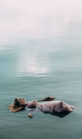 The girl lies peacefully with her eyes closed in the blue water. Copy space for text.
