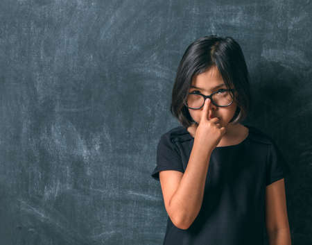 Back to school. Serious little girl adjusts his glasses near blackboard. Child from elementary school. Education.