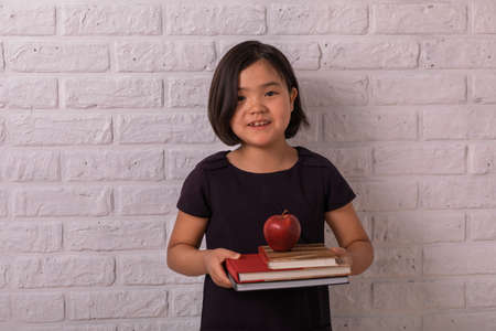 Back to school. Little girl holds books and an apple near a white brick wall. Child from elementary school. Education. Foto de archivo