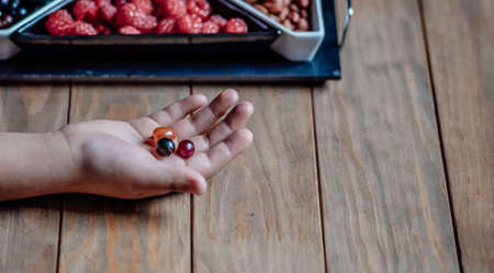 Child holds berries in the palm of his hand over a wooden table. Vases with raspberries and currants are lying on the table. Delicious food, dessert