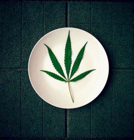 Cannabis leaf on a white plate. Floor tile background. cannabis live resin extraction on green background. Medical marijuana concept Top view