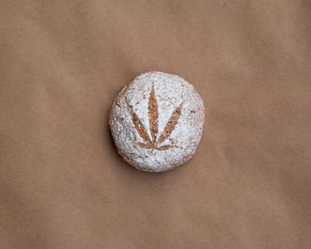 Pattern of cannabis leaf made with powdered sugar on the cookies on kraft background. Cannabis live resin extraction. Medical marijuana concept. Banner 版權商用圖片