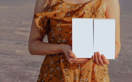Girl in a yellow dress holds two isolated white boxes in her hands outdoors