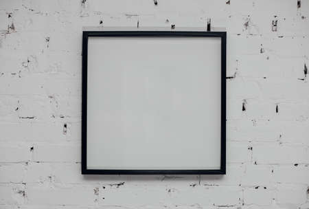 Blank picture frame at the brick wall