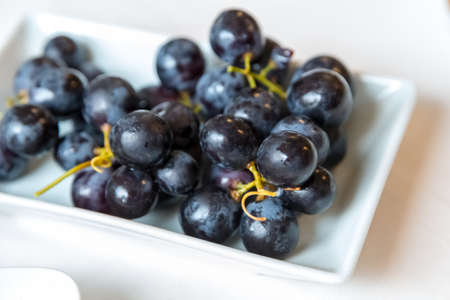 fresh black grapes in white plate on white background Zdjęcie Seryjne