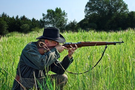crouches: Hunter crouches in the grass and aims his rifle