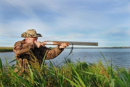 охотник: Duck hunter shoots his shotgun
