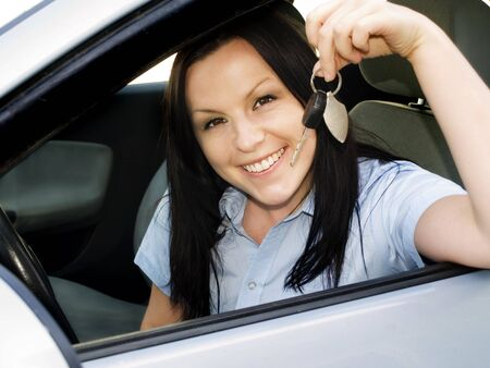 smiling woman holding key in the car Stock Photo