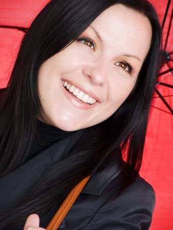 closeup of smiling brunette woman in fall clothes holding umbrella Stock Photo - 5675783