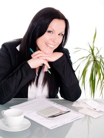 smiling brunette woman sitting with papers and calculator photo
