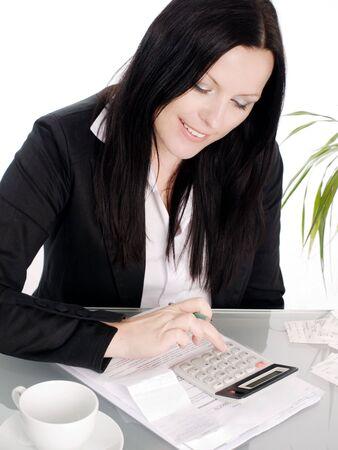 contabilidad financiera cuentas: sonriente mujer morena sentada con papeles y calculadora