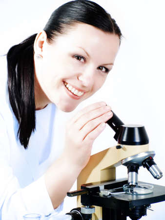 smiling brunette medical woman researching on a microscope