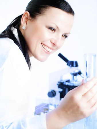 Closeup of a female researcher holding up a test tube