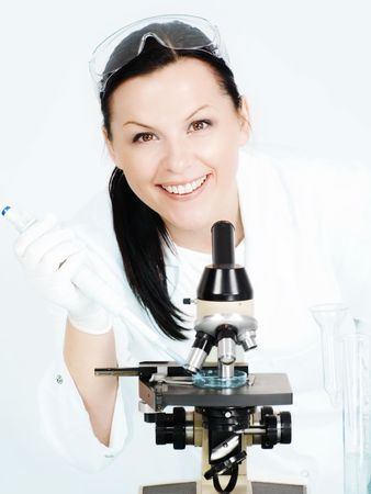 smiling brunette female researcher working on microscope in laboratory photo