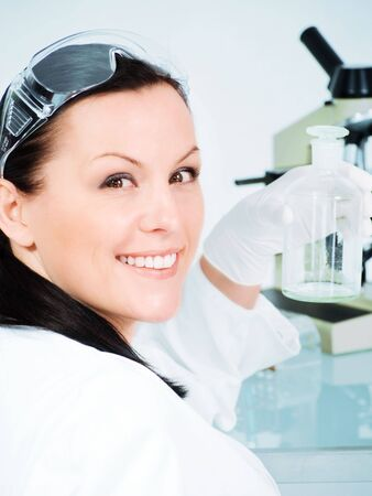 closeup of smiling brunette female researcher holding glass tube in laboratory photo