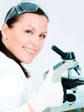 smiling young researcher show thumb up in laboratory photo