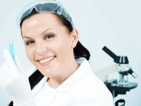 closeup of smiling female researcher holding test tube in laboratory photo