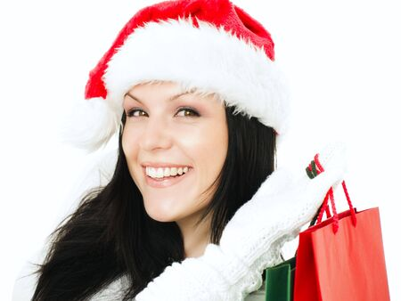 smiling woman in christmas clothes holding shopping bags over white photo