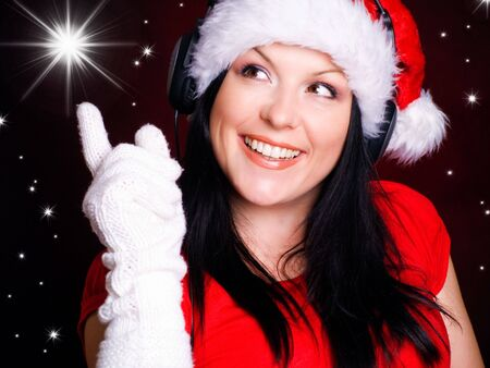 smiling christmas with headphones woman pointing star over red background photo