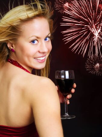 smiling blond woman holding wine and celebrating new year Stock Photo
