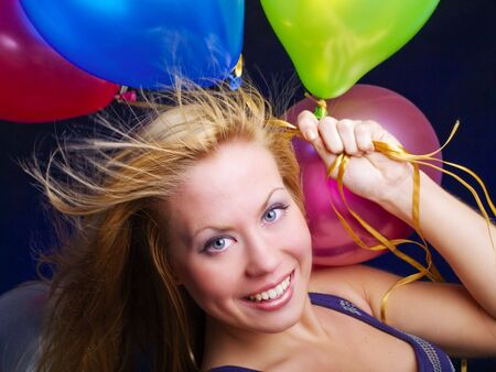 smiling woman holding ballons and celebrating photo