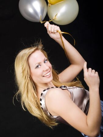 smiling woman holding balloons and celebrating photo