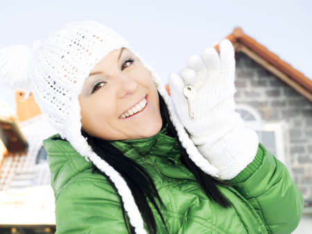 woman in winter clothes holding keys to the house photo