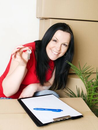woman with package holding keys to new apartment Stock Photo - 6525051