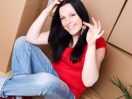 woman with package holding keys to new apartment Stock Photo - 6525050