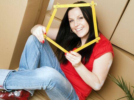 mujer con cajas de cart�n, sosteniendo la medici�n de la cinta Foto de archivo - 6525052